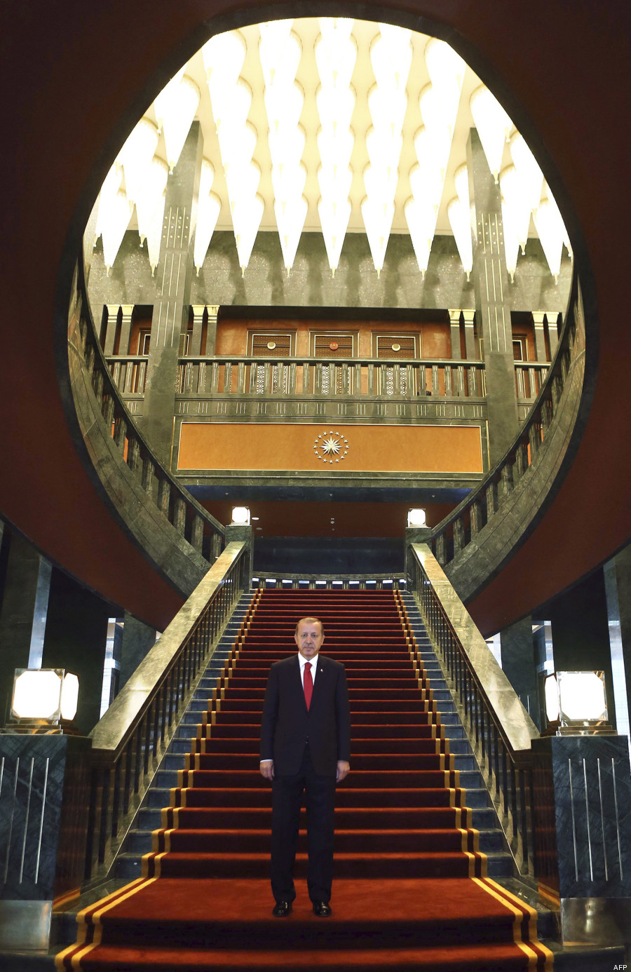 Turkish President Recep Tayyip Erdogan poses inside the new Ak Saray presidential palace (White Palace) on the outskirts of Ankara on October 29, 2014 before hosting a reception marking Turkey's annual republic day which celebrates the foundation of modern Turkey in 1923. Erdogan unveiled his new presidential palace on the outskirts of Ankara, denounced by ecologists as an environmental blight and by the opposition as new evidence of his autocratic tendencies.  An immense project built at a reported cost of $350 million, it has an area of 200,000 square metres, 1,000 rooms and architecture that is supposed to marry modernism and the traditions of the mediaeval Seljuk dynasty. AFP PHOTO/ADEM ALTAN